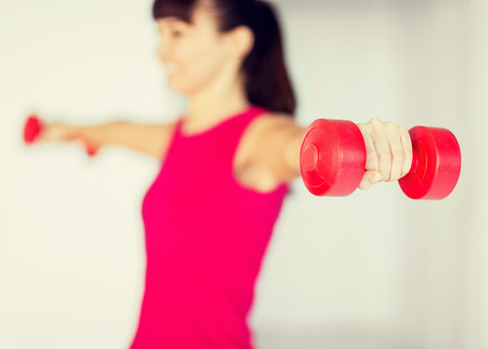 stamina: sport and recreation concept - sporty woman hands with light red dumbbells