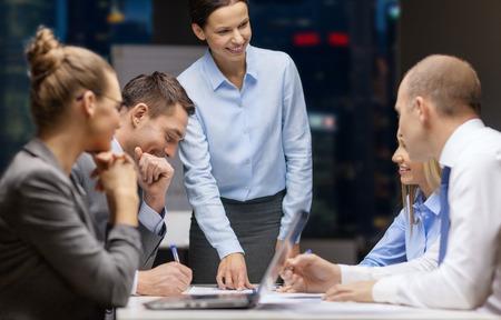 business, technologie, mensen, deadline en teamwork concept - glimlachende vrouwelijke baas te praten business group 's nachts kantoor achtergrond