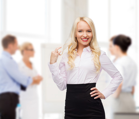 secretary skirt: business, team work and people concept - smiling businesswoman, student or secretary over group of colleagues in office background Stock Photo