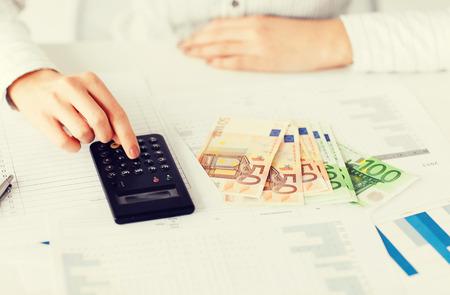zaken, kantoor, huishouden, school, belastingen en onderwijs concept - vrouw hand met rekenmachine en euro geld Stockfoto