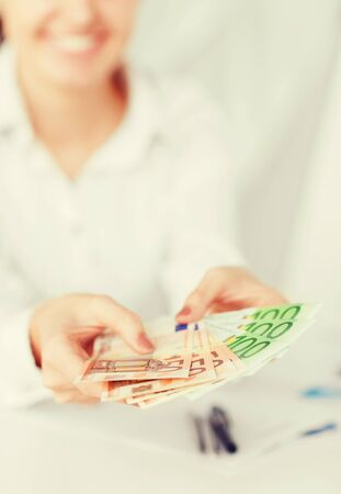 household money: business, office, household, banking, tax, gambling concept - woman hands with euro cash money