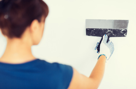 interior design and home renovation concept - woman plastering the wall with trowel photo