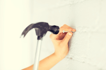 hammer: architecture and home renovation concept - architect hammering nail in wall
