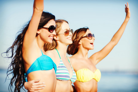 summer holidays and vacation - girls in shades and bikini walking on the beach