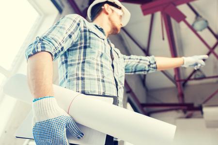 Architektur und Renovierungs-Konzept - ein Mann in Helm und Handschuhe mit Blaupause, die Richtung Standard-Bild