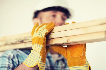 修理、建物しホーム コンセプト - 手袋とヘルメットの肩に木の板を運ぶ男性のクローズ アップ 写真素材