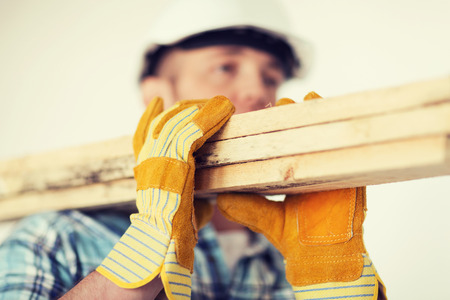 repair, building and home concept - close up of male in gloves and helmet carrying wooden boards on shoulder Stockfoto