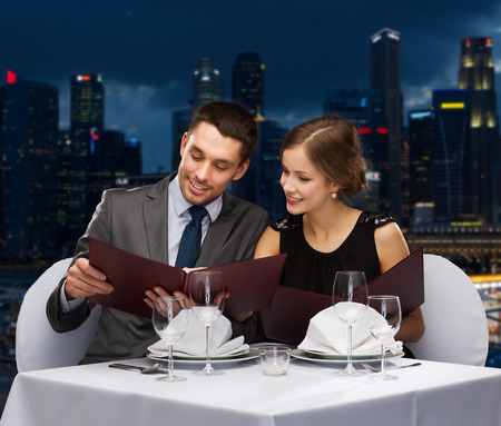 food, holidays and people concept - smiling couple with menus at restaurant over night city background Stock Photo