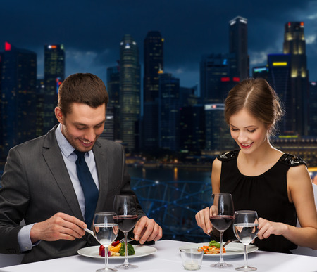 main course: people, celebration, romantic and holidays concept - smiling couple eating main course with red wine at restaurant over night city background