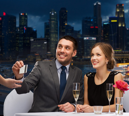restaurant, people and holidays concept - smiling couple paying for dinner with credit card at restaurant over night city background Banco de Imagens