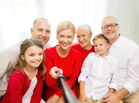 stick children: family, holidays, generation, christmas and people concept - smiling family with camera and selfie stick making picture at home