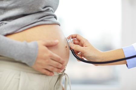 estetoscopio: embarazo, cuidado de la salud, las personas y concepto de la medicina - Cierre de vientre de la mujer embarazada y la mano del médico con el estetoscopio en la cita médica en el hospital