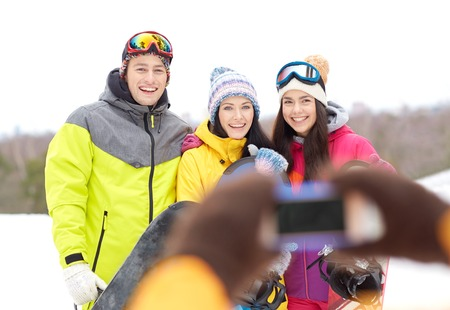 winter sport, leisure, friendship, technology and people concept - happy friends with snowboards and smartphone taking picture photo