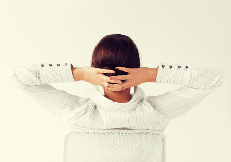 arms on chair: business, office, school and education concept - relaxed woman from the back with arms on head