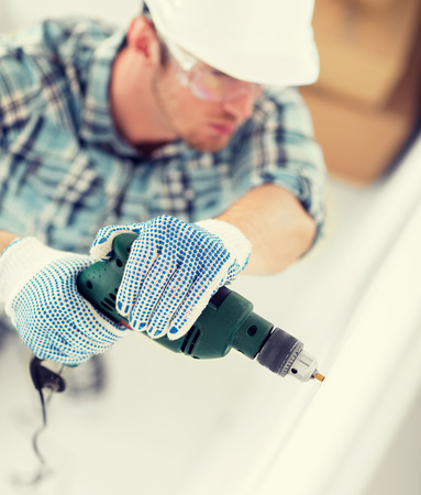 making hole: interior design and home renovation concept - man in helmet with electric drill making hole in wall Stock Photo