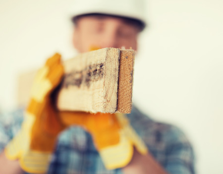 repair, building and home concept - close up of male in gloves and helmet carrying wooden boards on shoulder photo