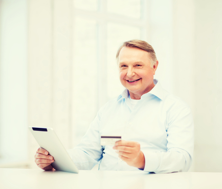 oldness: business, oldness, online banking, internet shopping and oldness concept - smiling old man with tablet pc and credit card at home