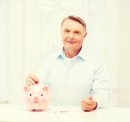 thrifty: savings, oldness,business and banking concept - old man putting coin into big piggy bank