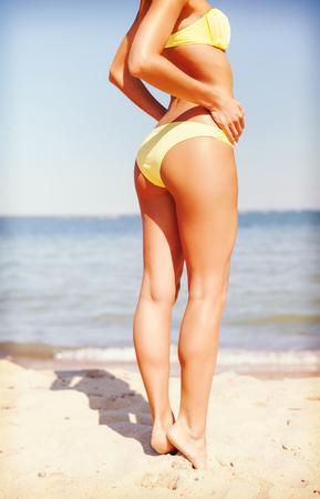 sexy beine: Sommerferien, Urlaub und Strand-Konzept - Mädchen posiert im Bikini am Strand