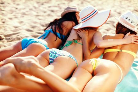 bottoms: summer holidays and vacation - girls in bikinis sunbathing on the beach