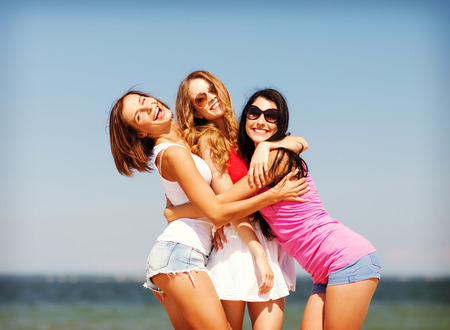 beach girl: summer holidays and vacation - group of girls having fun on the beach