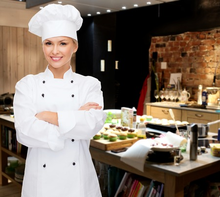 pastries: cooking, bakery, people and food concept - smiling female chef, cook or baker with crossed arms over restaurant kitchen background Stock Photo