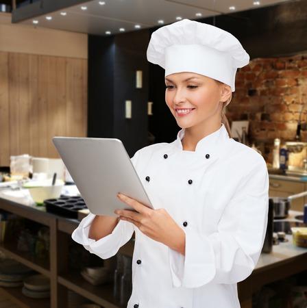 料理、人・技術・食品コンセプト - レストラン キッチンの背景の上の女性シェフ、クックやタブレット pc コンピューターとパン屋に笑みを浮かべて