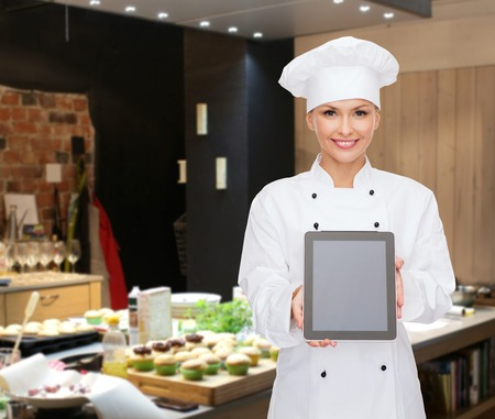 pastries: cooking, bakery, people, technology and food concept - smiling female chef, cook or baker showing tablet pc computer blank screen over restaurant kitchen background Stock Photo