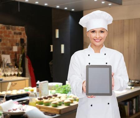 panadero: la cocina, la panadería, la gente, la tecnología y el concepto de alimentos - sonriente mujer chef, cocinero o panadero que muestra la pantalla en blanco tableta ordenador de la PC sobre la cocina del restaurante de fondo