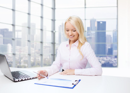 secretary desk: education, business and technology concept - smiling businesswoman with laptop computer and papers sitting over office room with city view window background