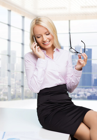 sexy teacher: education, business, technology, communication and people concept - smiling businesswoman or secretary holding eyeglasses and calling on smartphone over office room with city view window background