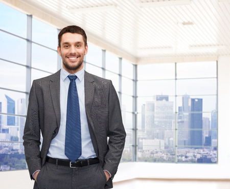 cheerful businessman: business, people and office concept - happy young businessman over office room or new apartment background