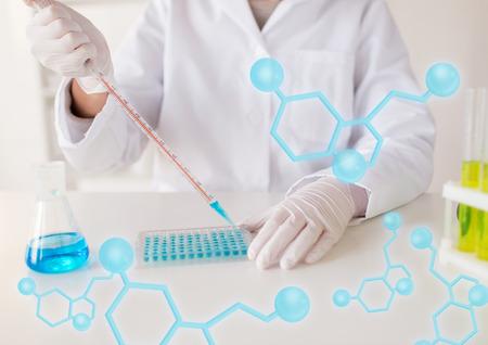 wetenschap, chemie, biologie, geneeskunde en mensen concept - close-up van jonge vrouwelijke wetenschapper met een pipet en kolf making test of het onderzoek in de klinische laboratorium
