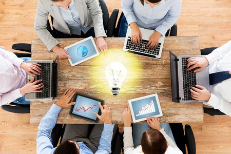Unternehmen, Menschen und Technologie-Konzept - Nahaufnahme von Kreativ-Team mit Laptop und Tablet-PC sitzen am Tisch im Büro über Glühlampe Standard-Bild - 37745670