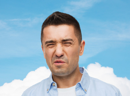 unpleasant smell: emotions, facial expression and people concept - man wrying of unpleasant smell over blue sky and cloud background Stock Photo