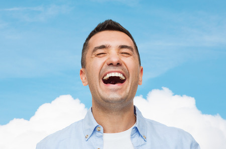 feelings of happiness: happiness, emotions and people concept - laughing man over blue sky and cloud background