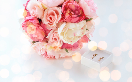 people, homosexuality, same-sex marriage and love concept - close up of gay female wedding rings in little box and flower bunch on table over holiday lights background photo