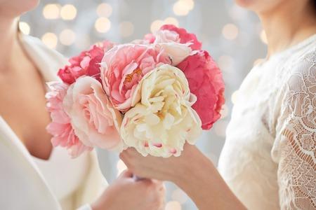 les gens, l'homosexualité, le mariage de même sexe et l'amour notion - gros plan heureux couple marié de lesbiennes avec bouquet de fleurs sur les lumières de vacances fond