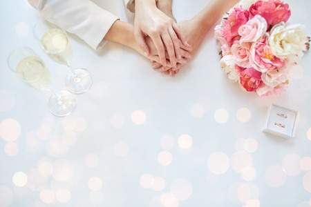 people, homosexuality, same-sex marriage and love concept - close up of happy lesbian couple hands with flower bunch, champagne glasses and wedding rings over holiday lights background Stock Photo