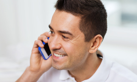 calling on phone: technology, people, lifestyle and communication concept - happy man calling on smartphone at home