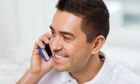 persona llamando: tecnología, gente, estilo de vida y el concepto de comunicación - hombre feliz llamando en el teléfono inteligente en el hogar