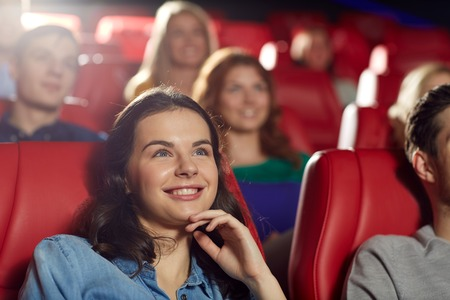 seat: cinema, entertainment and people concept - happy friends watching comedy movie in theater