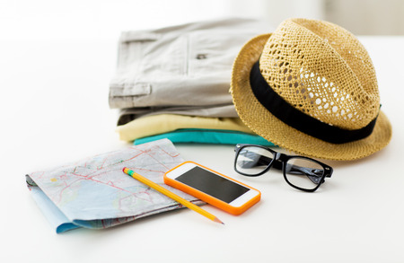 folded clothes: travel, summer vacation, tourism and objects concept - close up of folded clothes, smartphone and touristic map on table at home Stock Photo