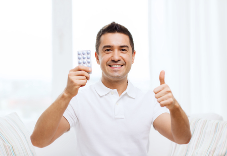 home health care: people, medication, medicine and health care concept - happy man showing thumbs up and holding pack of pills at home