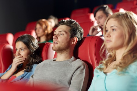 horror: cinema, entertainment and people concept - happy friends watching horror, drama or thriller movie in theater