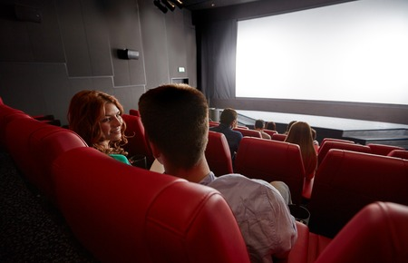 screening: cinema, entertainment, communication and people concept - happy couple of friends watching movie and talking in theater from back