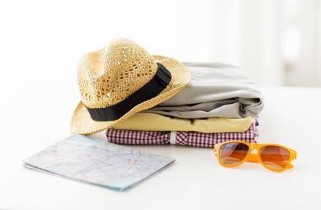 cestování, letní dovolená, cestovního ruchu a objekty koncept - zblízka skládaných oblečení a turistické mapy na stůl doma