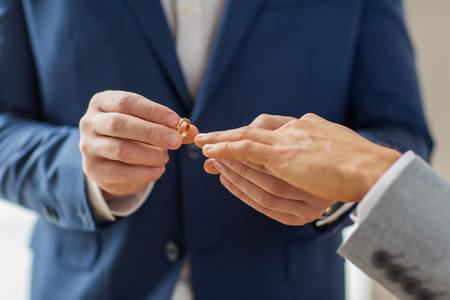 seks: mensen, homoseksualiteit, het homohuwelijk en liefde concept - close-up van gelukkige mannen homoseksueel stel handen zetten trouwring op
