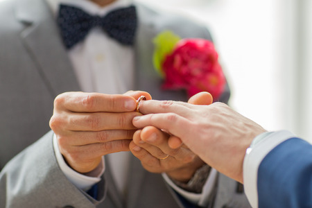 same sex: people, homosexuality, same-sex marriage and love concept - close up of happy male gay couple hands putting wedding ring on Stock Photo