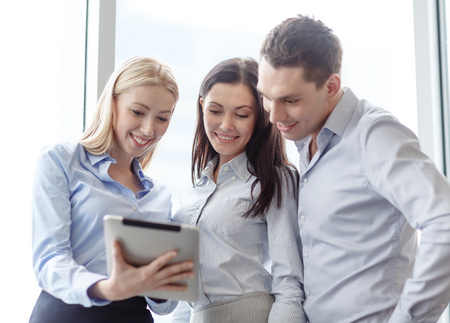 co work: business and office concept - smiling business team working with tablet pc in office